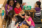 Education preschool 3 year olds teacher interacting with group of girls