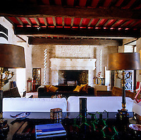 View over a table and a group of contemporary sofas towards the stone fireplace in the large living room