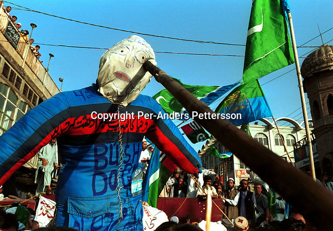 Demonstrators shouting insults to US President George Bush before burning a doll at a pro-Taleban demonstration on September 28, 2001 in the old town in Peshawar, Pakistan. A big demonstration was held after the Friday prayer supporting of Osama Bin Laden and the Taleban movement in Afghanistan..Photo: Per-Anders Pettersson....