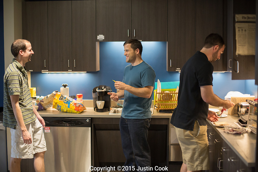 From left: Data Scientist Colin Feeney and Chief Revenue Officer Adam Smith joke in the kitchen while intern Austin Bello (ALL CQ) makes lunch at the Automated Insights office in Durham, N.C. on Thursday, May 7, 2015. An Automated Insights algorithm was recently pitted against an NPR reporter to see who could write the best news brief about a Denny's earnings report. (Justin Cook)