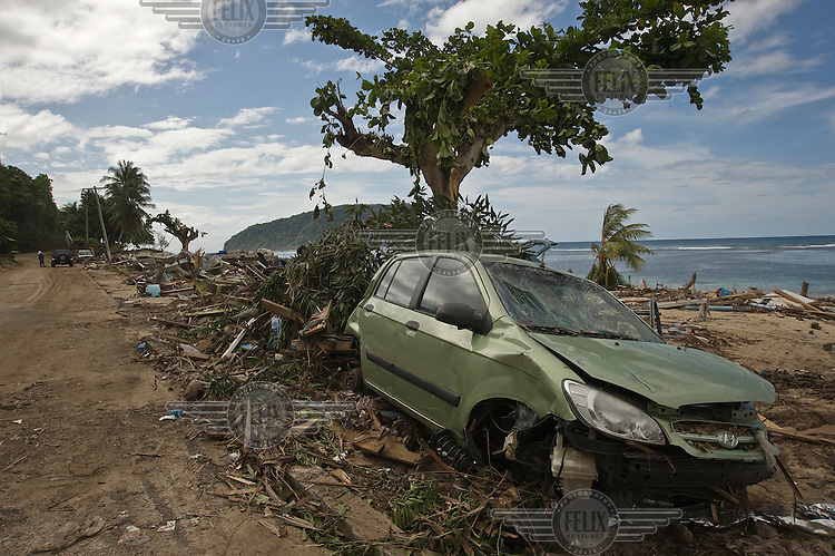 A car amongst the debris strewn across the beach at Lalomanu. More than 170 people died when a tsunami triggered by an 8.3 magnitude earthquake hit Samoa and neighbouring Pacific islands on 29/09/2009. Samoa (formerly known as Western Samoa)..