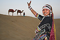 Rajasthani dancer in traditional costume performing on sand dunes in the Thar Desert; Camel driver with camels in background; Rajasthan, India ---Model Released