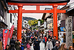 People passing through a red Torii gate at the exit of Fushimi Inari Taisha Shinto shrine in Fushimi Ward, Kyoto, Japan 2017