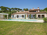 The rear of the large house in Cap d'Antibes showing the series of French windows which open onto the terrace and outdoor swimming pool
