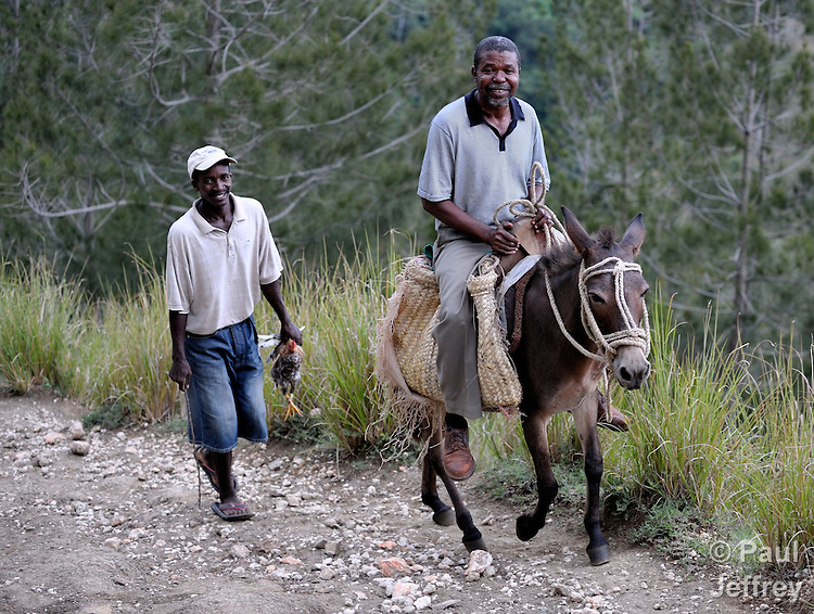 Paul Prevost rides a donkey in the hills outside of Mizak, a remote haitian village. Prevost is co-founder of Haitian Artisans for Peace Internaitonal.