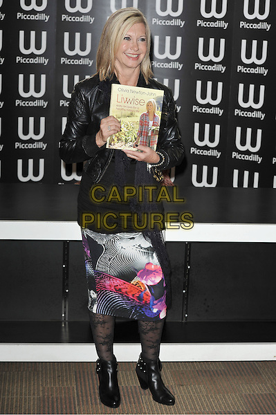 Olivia Newton-John.attended her 'Livwise: Easy Recipes For A Healthy, Happy Life' booksigning session, Waterstone's, Piccadilly, London, England..April 19th, 2012.full length black leather jacket top white blue pink print skirt pattern tights ankle boots book.CAP/MAR.© Martin Harris/Capital Pictures.