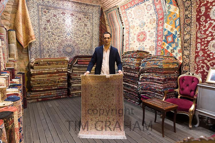 Salesman With Traditional Turkish Carpet Rug In The Grand Bazaar Kapalicarsi Great Market