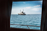 GALAPAGOS ISLANDS, ECUADOR, Isabela Island, Punta Vicente Roca, a boat passing by seen through a window on the M/C Ocean Spray