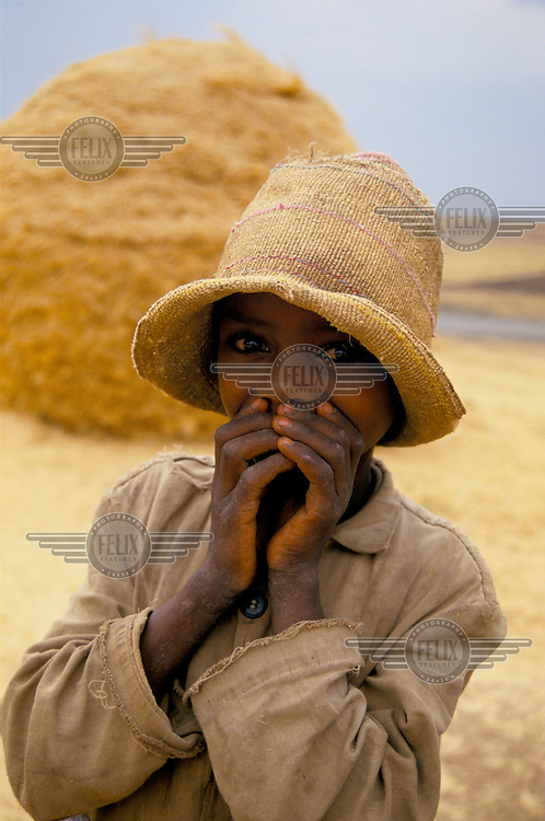 A child with a straw hat in front of a haystack.