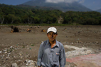 Jorge Mario Gerónimo Lopez stands in an area of Panabaj, Guatemala on Tuesday, March 20, 2007. A deadly mudslide here was spawned by rains associated with Hurricane Stan in October 2005. Initially, up to 500 Tzujutil Maya villagers were believed to have been killed by the mudslide, which essentially  wiped away the town. Mario was able to escape with his family in the early morning hours as the slide hit. The areas where he stands once featured the homes of villagers. Forensic anthropologists from the Fundación de Antropología Forense de Guatemala have been working to unearth the bodies of the missing and have recovered more than 100. They have also found the number of missing to be lower than originally thought, after many people were located in shelters or living in other towns after the disaster.