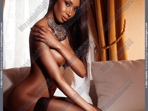 Beautiful glamorous sexy half nude black woman in stockings sitting on a white sofa in a dimly lit room, artistic glamour photo.