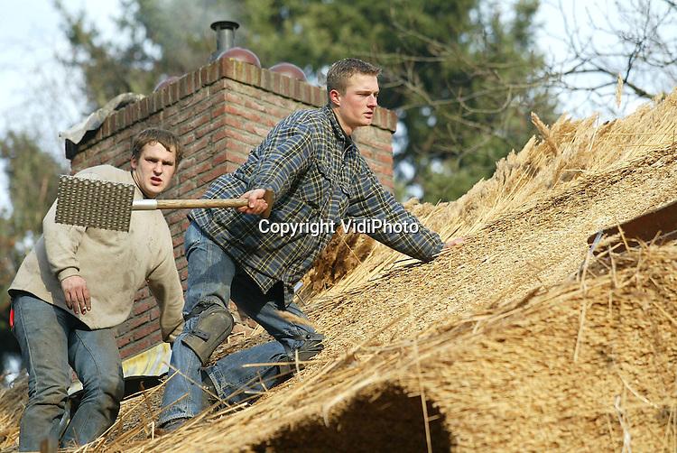 Foto:  VidiPhoto..AMERSFOORT - Personeel van dakdekkersbedrijf Wout Hazeleger uit Kootwijkerbroek vervangt het oude rieten dak van het kantoor van Dierenpark Amersfoort. Het oude dak heeft het bijna 50 jaar volgehouden, 15 jaar langer dan gebruikelijk. Toen het echter tijdens regenbuien ook binnen begon te druppelen, werd er deskundige hulp ingeroepen. Het is de bedoeling dat het nieuwe rieten dak er voor de jaarwisseling op zit.