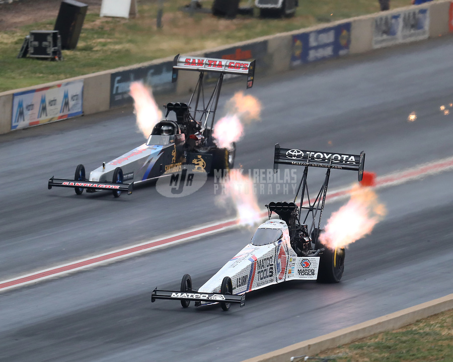 Jul 21, 2018; Morrison, CO, USA; NHRA top fuel driver Antron Brown (near) races alongside Gregory Carrillo during qualifying for the Mile High Nationals at Bandimere Speedway. Mandatory Credit: Mark J. Rebilas-USA TODAY Sports
