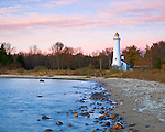 Alcona County, MI: Pink clouds of sunrise over Sturgeon Point Lighthouse (1870) on Lake Huron in autumn