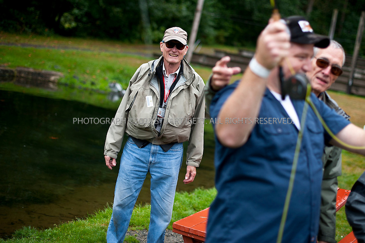 "9/17/2011--Orting, WA, USA..Jim McRoberts (left), a veteran and member of Healing Waters, helps teach younger veterans fly fishing at Bill's Fly Fishing Hole in Orting. WASH., about an hour's drive from Seattle...Healing Waters is a national nonprofit organization, founded to help disabled active-duty personnel and veterans by helping them, at no cost, to relearn fine motor skills and connect with other veterans, simply by learning the art of fly-fishing. It's an example of the kind of out-of-the-box thinking that is going into battling the devastating psychological effects of war. Some Healing Waters participants are in wheelchairs, missing limbs or just struggling with the transition to civilian life. Some suffer from PTSD, a condition that many say is like reliving hell. ..PTSD is an anxiety disorder brought on by a traumatic, life-threatening event. It is prevalent among combat veterans, but can also be experienced by civilians, including survivors of assault, rape, terrorist attacks, natural disasters and even extreme car accidents. Experts sometimes refer to it as the ""signature wound"" of our current conflicts in Iraq and Afghanistan, although statistics on the number of soldiers with PTSD remain vague. Studies report that it can occur in anywhere between 5 and 35 percent of soldiers returning from combat - or ""theater"" as it is referred to in the military. In 2010, 171,423 deployed Iraq and Afghanistan war veterans were diagnosed with PTSD, out of 593,634 patients treated by the VA--nearly one-third of them. And it's likely that diagnoses will continue to increase due to current soldiers experiencing multiple deployments--and thus, potentially longer exposure to trauma....©2011 Stuart Isett. All rights reserved."