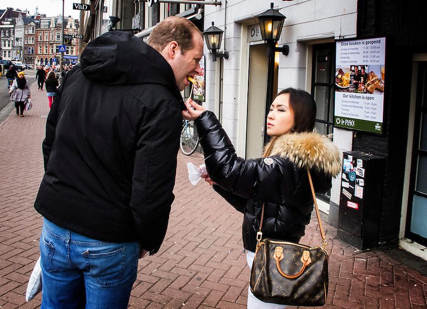 Nederland, Amsterdam, 10 april 2013.Toeriste voert haar vriendje een patatje..Foto(c): Michiel Wijnbergh