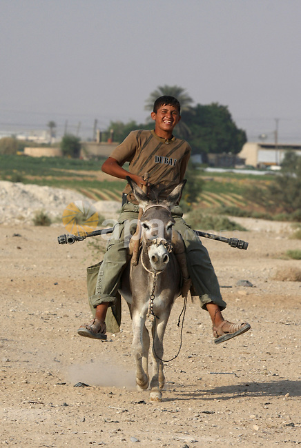 A Palestinian boy smiles as he rides on donkey , in West Bank city of Jericho , on Oct. 11.2010 . Jericho is one of the oldest continuously inhabited cities in the world, with evidence of settlement dating back to 9000 BC,it has a population of over 20,000 Palestinians. Situated well below sea level on an east-west route 16 kilometres (10 mi) north of the Dead Sea, Jericho is the lowest permanently inhabited site on earth . Photo by Eyad Jadallah