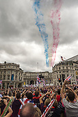 Trafagar Square, London, Engand. The red arrows fly past streaming red white and blue over the crowds with Union Jack flags.