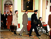 United States President Bill Clinton's defense team leaves the U.S. Capitol in Washington, D.C. after the first day of the U.S. House Impeachment presentation on 14 January, 1999.  Identifiable in the photo, from left: Bruce Lindsey, in black coat with black brief case; Nicole Seligman, in brown coat with brown brief case; David Kendall, in light coat with battered brief case; two police officers; and Charles Ruff, in the wheel chair..Credit: Ron Sachs / CNP