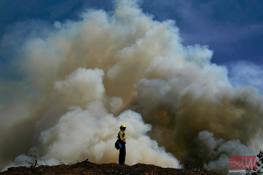 SANTA BARBARA,CA - JULY 4, 2008: A firefighter is dwarfed by smoke from fire burning along West Camino Cielo Road, July 4, 2008.  The fire has doubled to 5,400 acres and triggered more evacuations but has not destroyed any homes. Residents of more than 1,700 homes remained under evacuation orders.