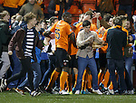Dundee Utd fan runs onto the pitch and takes a selfie of himself as the players celebrate Blair Spittal's goal