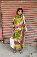 Bangladesh, Jhenaidah. Fazila, along with many others stands in the street with her tools looking for part-time labor. She works about  2-3 days a week, making about 1000 TK per week, about US$15. She works in carpentry, making cement, food, clothing. Model released.