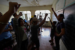 "Larren Jo ""LJ"" Bacilio (right), a teacher in the Alternative Learning System of the Kapatiran-Kaunlaran Foundation (KKFI), raises a fist with his students at the end of a class in the Tondo neighborhood of Manila, Philippines. <br /> <br /> KKFI is supported by United Methodist Women."