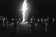 Dunham Springs, LA. December 1976.<br /> The members of Ku Klux Klan at a night ceremony which takes place ones a month; wearing white hoods and with the cross on fire. The local group consists of 50 members; half of which are women. The leader of the cell is Bill Wilkinson who is also the leader of The National Movement, going by the title of &quot;Imerial Magician of the Invisible Empire of Horsemen of the KKK&quot; The motto of the order is &quot;Be vigilant to Protect the white race.&quot; After the night ceremony, the members get together for dinner, preceded by a prayer.