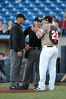 Quad Cities River Bandits manager Omar Lopez #22 argues a call with umpires Jeremie Rehak and Charlie Ramos during a game against the Wisconsin Timber Rattlers on May 24, 2013 at Modern Woodmen Park in Davenport, Iowa.  Quad Cities defeated Wisconsin 4-3  (Mike Janes/Four Seam Images)