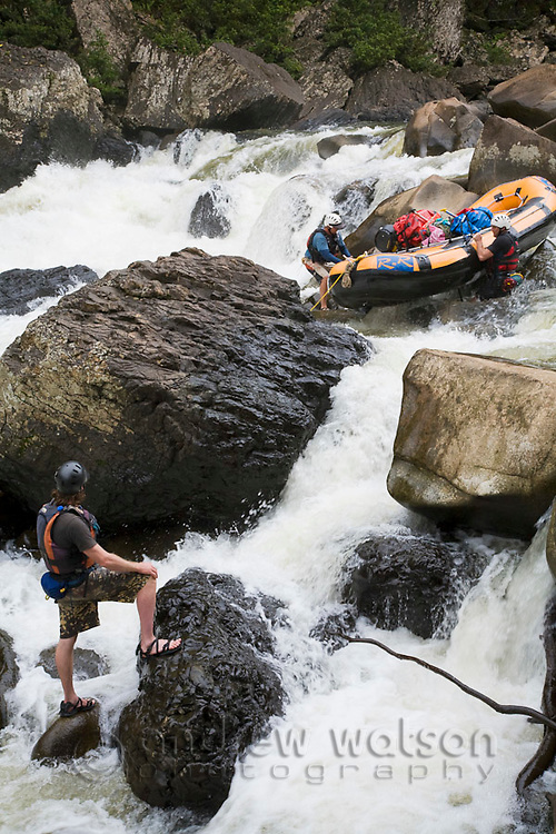 River guides drag their raft over rocks during a rafting expedition on the North Johnstone River, Wooroonoonan National Park, Queensland, Australia