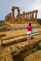 Agrigento, tourist taking a photo at Temple of Juno (Tempio di Giunone), Valley of the Temples (Valle dei Templi), Sicily, Italy, Europe. This is a photo of a tourist taking a photo at The Temple of Juno (Tempio di Giunone) at The Valley of the Temples (Valle dei Templi), Agrigento, Sicily, Italy, Europe.