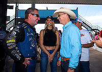 Oct 16, 2016; Ennis, TX, USA; NHRA funny car driver Tommy Johnson Jr (left) talks with professional bull rider Ty Murray (right) and finance Paige Duke during the Fall Nationals at Texas Motorplex. Mandatory Credit: Mark J. Rebilas-USA TODAY Sports