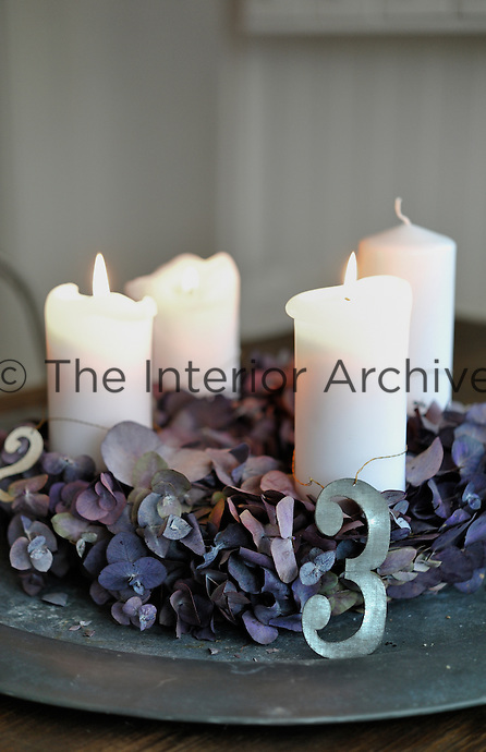 Four pillar candles surrounded by zinc numbers and dried hydrangea petals make an attractive display on the dining table
