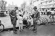 April 1970, Ho Chi Minh City, Vietnam --- Two soldiers talk with a group of Vietnamese children selling balloons along the street near a public square in Saigon. --- Image by © JP Laffont