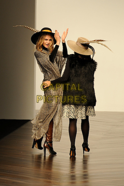 Cara Delevingne & Daniella Helayel .attended the Issa London LFW a/w 2013 catwalk show, LFW day 2, BFC Showspace, Somerset House, The Strand, London, England..February 16th, 2013.London Fashion Week full length catwalk runway feathers gold silver brown hat dress crochet tights arms hands looking over shoulder clapping back behind rear fur.CAP/MAR.© Martin Harris/Capital Pictures