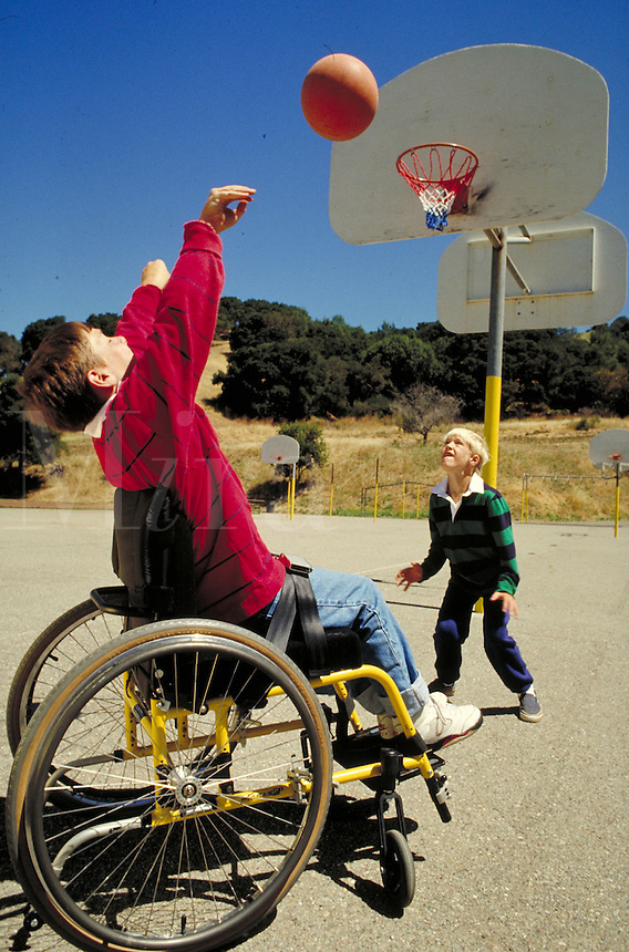 CAUCASIAN BOY IN A WHEELCHAIR SHOOTING HOOPS WITH HIS FRIEND AT A BASKETBALL COURT AT SCHOOL. BOYS, ONE IN A WHEELCHAIR. OAKLAND CALIFORNIA USA.