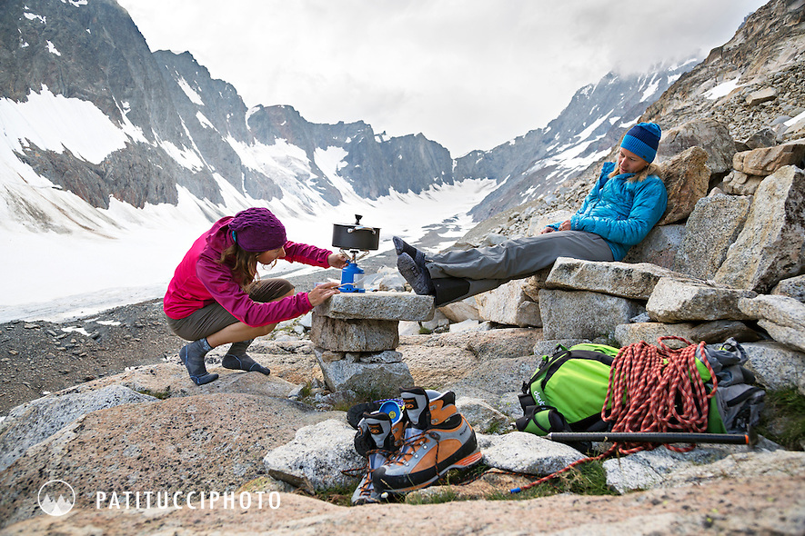 Two female hikers sitting at the Aarbiwak cooking on a camp stove. Switzerland