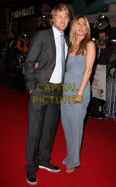 "OWEN WILSON & JENNIFER ANISTON.""Marley & Me"" UK film premiere held at Vue cinema, Leicester Square, London, England..March 2nd, 2009. .full length blue long maxi dress strapless gold necklaces chains Burberry silk down beige black trainers grey gray suit tie floor-length georgette hand in pocket.CAP/ROS.©Steve Ross/Capital Pictures."