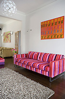 In the living room the brightly coloured abstract painting and purple-and-pink striped sofa have been juxtaposed to create a bold and confident statement