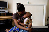 "Thania, from DR Congo, with one of her two children born after she was forced into prostitution, in the bedsit where she now stays. She arrived in the UK in September 2004 claiming asylum after her family were murdered by Congolese soldiers. She was forced to watch her brother burned to death after a tyre was set alight around his neck. She was raped but managed to escape. After her claim was refused she walked the streets begging people for food and money, ""I couldn't think properly because I was so hungry."" Thania is one of an estimated 300,000 rejected asylum seekers living in the UK. ."