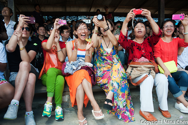 A crowd of Chinese tourists cheer during the elephant show, where the animals perform stunts such as football and painting at Nong Nooch Tropical Botanical Garden in Pattaya, one of the most frequented attractions in the city.