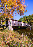 Scenic view of fall foliage and the the Halls Mill covered bridge spanning the Neversink River. Clargville, New York.