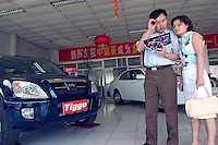 A couple look at a brochure of Chery at a showroom in Beijing, China..24 May 2005