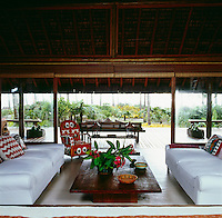The living room with white sofas and African beadwork armchair opens on to the deck via sliding glass doors