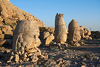 Statue heads, from left, Zeus, Apollo,  Herekles Eagle, & Lion with headless seated statues in front of the stone pyramid 62 BC Royal Tomb of King Antiochus I Theos of Commagene, east Terrace, Mount Nemrut or Nemrud Dagi summit, near Adıyaman, Turkey