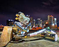This is a slightly different view of the traveling man sitting and playing his banjo near the train station at night in the Deep Ellum district of downtown with the city skyline.