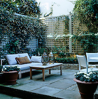 A pair of Moroccan lanterns stand on a table in the small and secluded courtyard garden