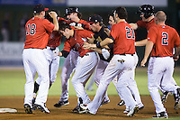 Brett Austin (20) is mobbed by teammates after hitting a walk-off 2-run double to cap a four run rally in the bottom of the ninth inning against the Asheville Tourists at Intimidators Stadium on June 25, 2015 in Kannapolis, North Carolina.  The Intimidators defeated the Tourists 9-8.  (Brian Westerholt/Four Seam Images via AP Images)