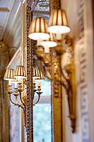 A detail of a pair of gilt wall lamps either side of a mirror.