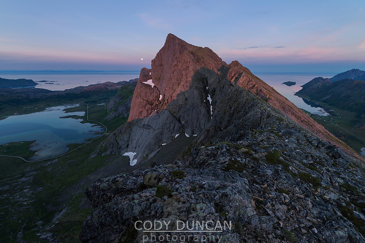 Midnight sun light illuminates Stortind mountain peak, Flakstadøy, Lofoten Islands, Norway